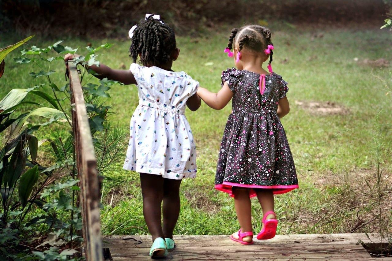 Duas crianças caminham de mãos dadas