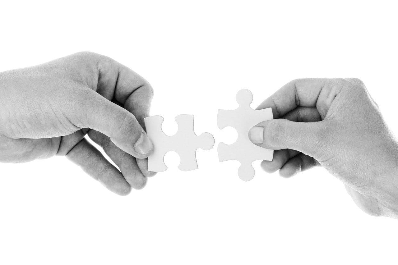 Imagem mostra uma pessoa encaixando peças de quebra-cabeça