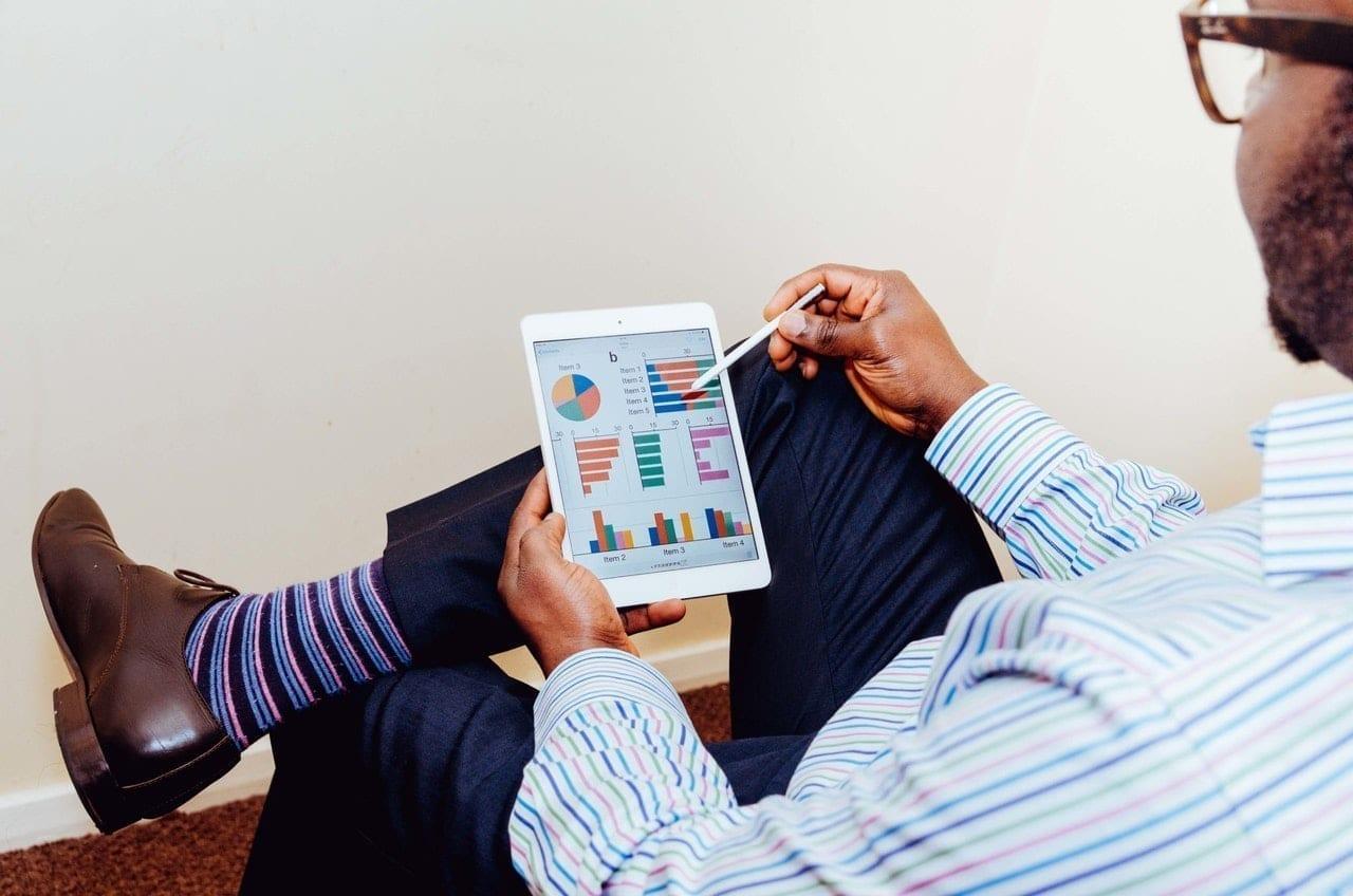 Um homem examina indicadores em um iPad