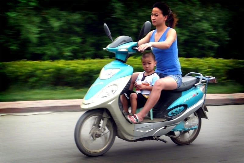 Mãe e filho em moto elétrica na China