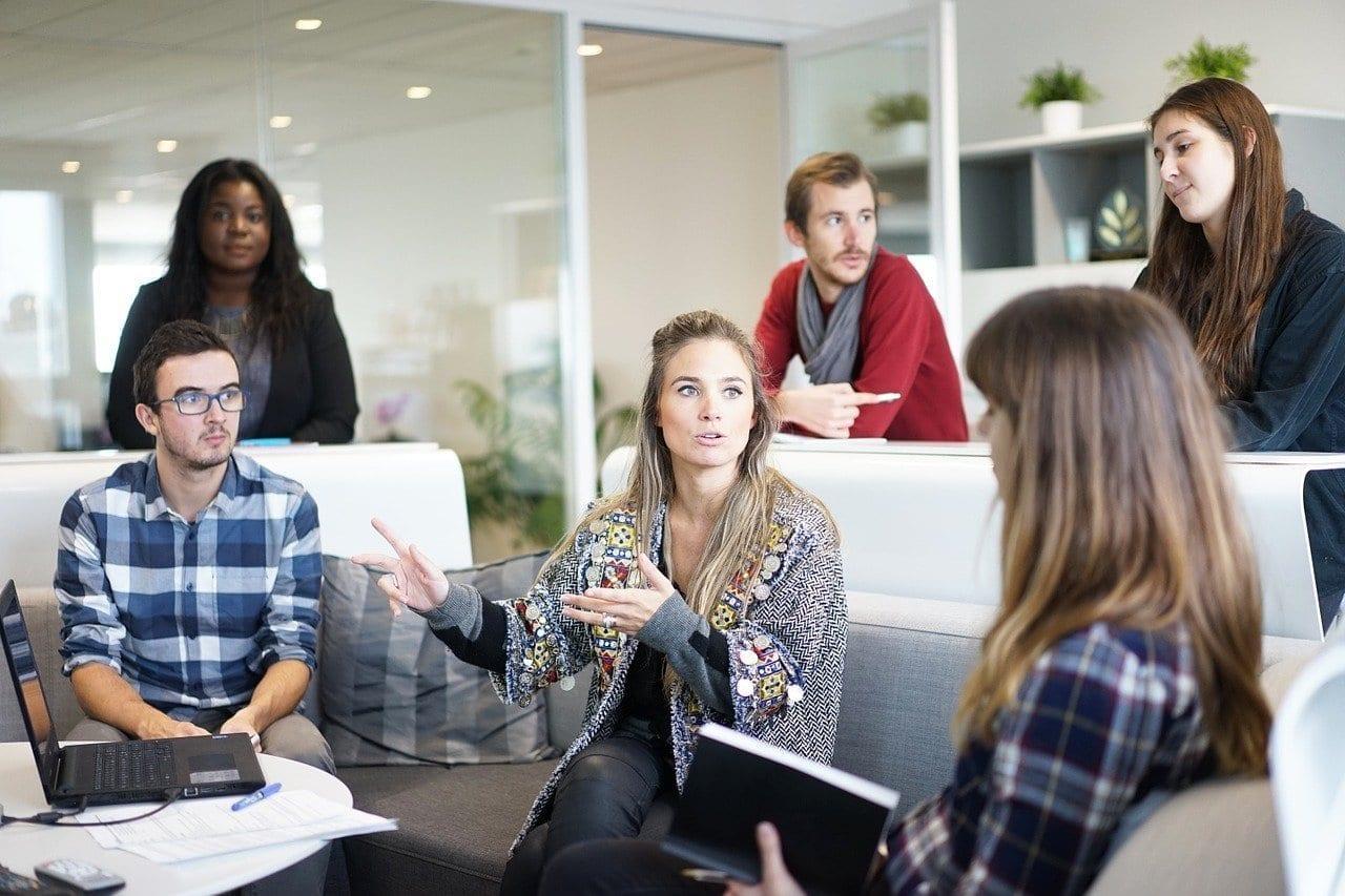 Pessoas conversam e gesticulam em reunião no escritório