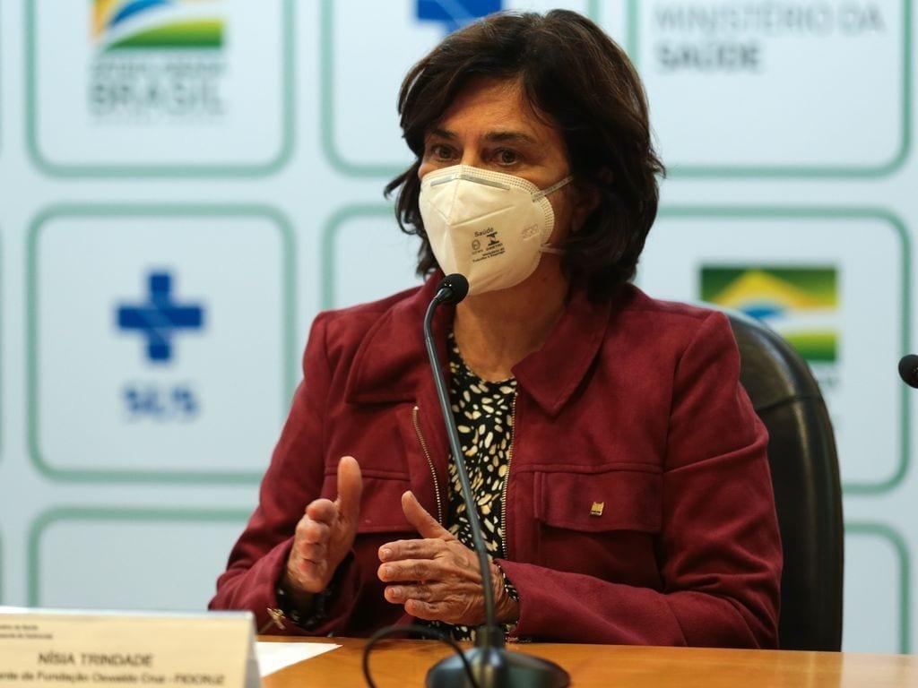 Nísia Trindade, presidente da Fiocruz, está usando máscara enquanto fala em coletiva de imprensa no ministério da Saúde