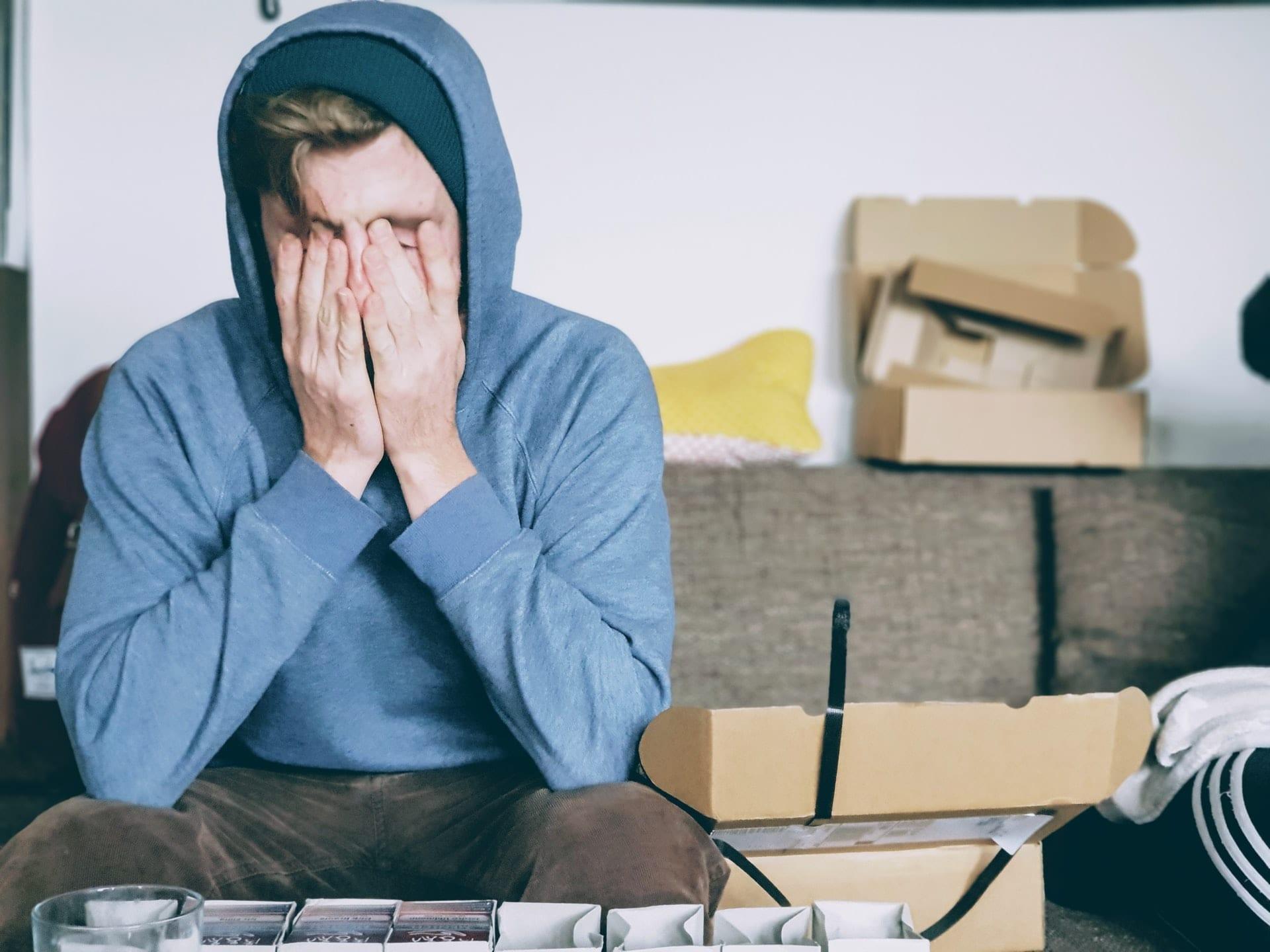 Imagem mostra pessoa sofrendo de fadiga, esfregando o rosto